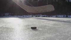 SLOW MOTION CLOSE-UP: Hockey player hitting puck on frozen lake Stock Footage