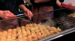 Osaka, JP - January 24, 2015:   Takoyaki (Octopus balls) being prepared at - stock footage