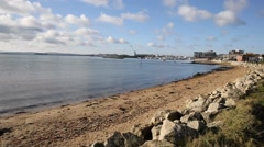 Sea lapping on beach view Poole harbour and quay Dorset England UK - stock footage
