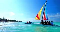 4K Catamaran Sailing on Azure Ocean to White Sand Tropical Beach Stock Footage