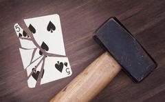 Hammer with a broken card, five of spades Stock Photos
