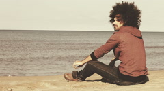 Sad lonely man sitting on the beach thinking Stock Footage