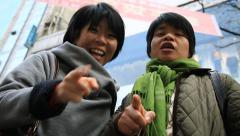 Two asian women pointing the camera with their fingers and laughing each other Stock Footage