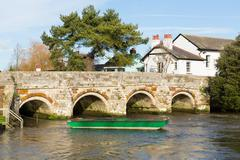 Bridge over the river River Avon Christchurch Dorset England UK and green boat Stock Photos