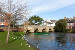 Dorset River Avon in Christchurch UK with boat and bridge - stock photo