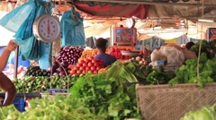 Latinos people watching TV while selling fruits and vegetable in market Stock Footage