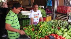 Latino man cleaning his vegetable stand at market Stock Footage