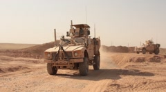Two armored vehicles MRAP driving out military base, Afghanistan Stock Footage