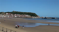 BEACH, CASTLE & LIGHTHOUSE, SOUTH BAY, SCARBOROUGH, NORTH YORKSHIRE Stock Footage