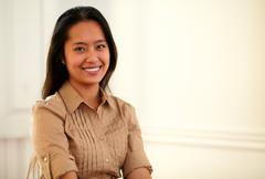 Stock Photo of Young asiatic woman smiling at you