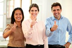 Professional team smiling at you with ok thumb Stock Photos