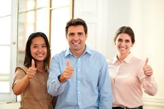 Male and female coworkers with ok sign - stock photo