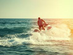 Silhouette of strong man jumps on the jetski above the water at sunset Stock Photos