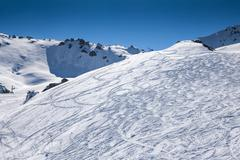 Freeride tracks on powder snow on background beautiful mountains and blue sky Stock Photos