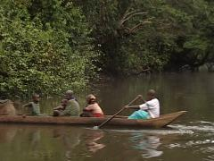Bantu people using a canoe to transport basket with food Stock Footage