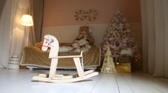 Children Rocking Horse swinging, christmas tree, sofa, soft toys, floor lamp Stock Footage