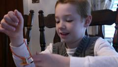 4K - Seven year old boy playing with toy bracelet Stock Footage