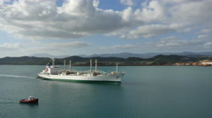 New Caledonia Noumea ship with green waterline and tug escort Stock Footage