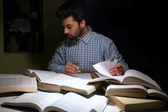 Male Indian student studying hard for exams. Stock Photos