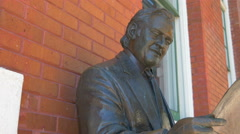 4K pan up from plaque to statue of man with newspaper Ybor City Stock Footage