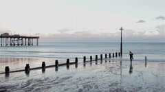 Little Girl and Mother Play in Sea by Sunset Over Teignmouth Pier Stock Footage