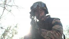 Soldier holding a gun with the sun behind Stock Footage