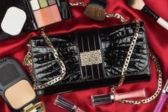 Beautiful bag from patent leather and cosmetics lying on red satin - stock photo