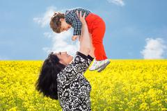 Mom raise uop her son in canola field - stock photo