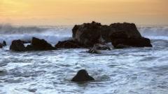 Pacific ocean sunset, waves splash on rocks - 60fps  Stock Footage
