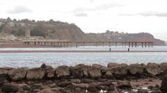 People Walk Past Teignmouth Pier on Beach Sand Bank Towards Sea Stock Footage