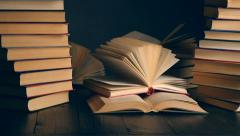 Old books on wooden deck table and dark background Stock Footage