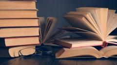 Old books on wooden deck table and dark background. UHD, 4K Stock Footage