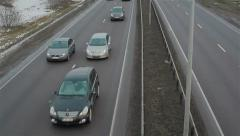 Winter highway - traffic on snow covered road, passing cars, view from bridge. V - stock footage