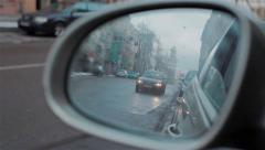 Back road reflected in car mirror, evening street with buildings and moving cars Stock Footage