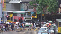 Pedestrian people umbrella cross busy street Hong Kong rainy day tram transit  Stock Footage