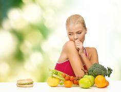 doubting woman with fruits and hamburger - stock photo