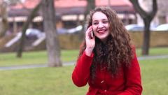 Girl in a red coat on a park bench - funny talking on the phone laughing Stock Footage