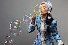 Image of snow maiden blowing soap bubble - stock photo