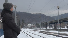 Impatience young woman wait train station winter cold day mountain village girl  Stock Footage
