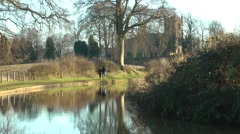 Walkers on canal towpath old church in background Stock Footage
