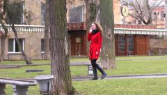 Bright girl in red coat walking in park talking on phone joyfuly and carefree Stock Footage