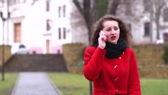 Bright beautiful girl in red coat walking talking on her phone anxiously Stock Footage