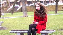 Girl in a red coat on a park bench using her smart phone waiting for young man Stock Footage