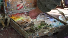 Artist mixes oil paints on a palette - stock footage