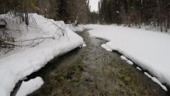 Stock Video Footage of Snow covered frozen river in forest, aerial view.
