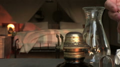 Hand with match lighting old fashioned oil lamp with safari tent in background Stock Footage