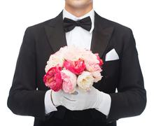 Man in tail-coat with flower bouquet Stock Photos