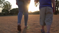 Mother and four year old boy holding hands and walking into setting sun Stock Footage