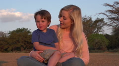 Four year old boy sitting on mothers lap and interacting Stock Footage
