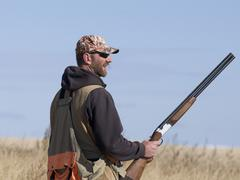 Hunter with gun at hip thinking what his next move will be Stock Photos